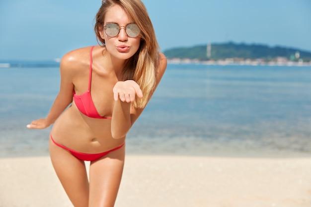 Zdjęcie ładnie Wyglądającej, Uroczej Młodej Kobiety Odpoczywa Podczas Letnich Wakacji, Nosi Czerwone Stroje Kąpielowe, Całuje Powietrze, Pozuje Przed Widokiem Na Ocean Z Miejscem Na Reklamę Lub Tekst Darmowe Zdjęcia