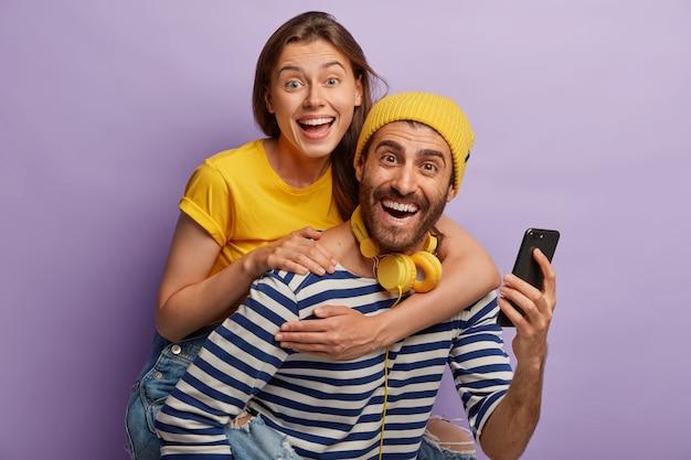 Zdjęcie Młodego Chłopaka I Dziewczyny Bawią Się Razem, Mężczyzna Daje Kobiecie Przejażdżkę Na Barana, Używać Telefonu Komórkowego, śmiać Się Radośnie, Odizolowane Na Fioletowej ścianie. Szczęśliwi Blogerzy Darmowe Zdjęcia