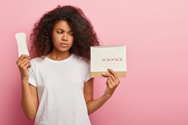 Zdjęcie Niezadowolonej Uroczej Kobiety Z Kręconymi Włosami Patrzy Na Kalendarz Z Zaznaczonymi Dniami Pms Darmowe Zdjęcia