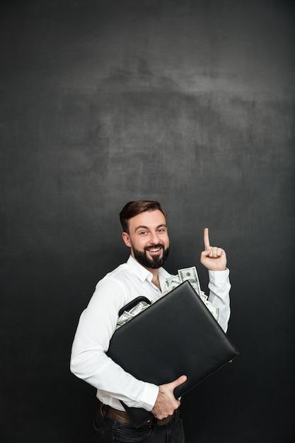 Zdjęcie Optymistycznego Człowieka, Który Raduje Się Swoją Nagrodą, Przytulając Czarną Teczkę Z Dużą Ilością Gotówki W środku, Wskazując W Górę Na Białym Tle Nad Ciemnoszarym Darmowe Zdjęcia