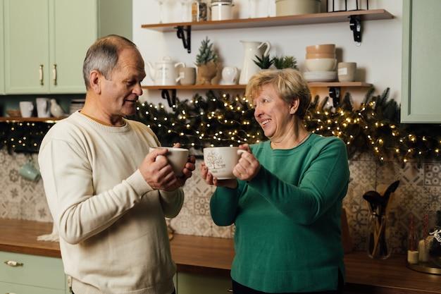 Zdjęcie Pary Starszych Lat 60. Cieszących Się życiem W Kuchni Z Kubkami Kawy. Walentynki Zakochanych Par. Zatrzymać Dyskryminację Ze Względu Na Wiek. Wysokiej Jakości Zdjęcie Premium Zdjęcia