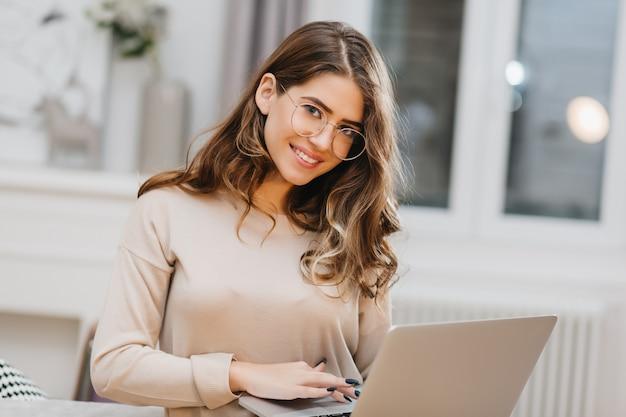 Zdjęcie Pięknej Białej Kobiety W Okularach Przy Użyciu Komputera Z Czarującym Uśmiechem Darmowe Zdjęcia