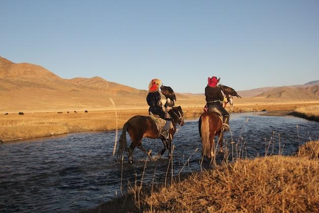 Zdjęcie Przedstawiające Dwóch Jeźdźców W Rzece Otoczonej Bezludną Doliną Ze Wzgórzami Darmowe Zdjęcia
