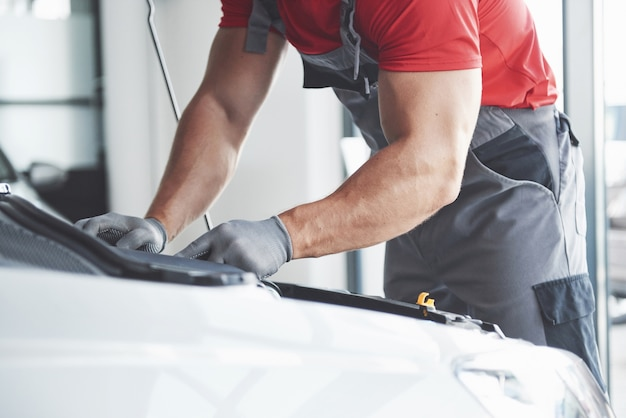 Zdjęcie Przedstawiające Umięśnionego Pracownika Serwisu Samochodowego Naprawiającego Pojazd. Darmowe Zdjęcia