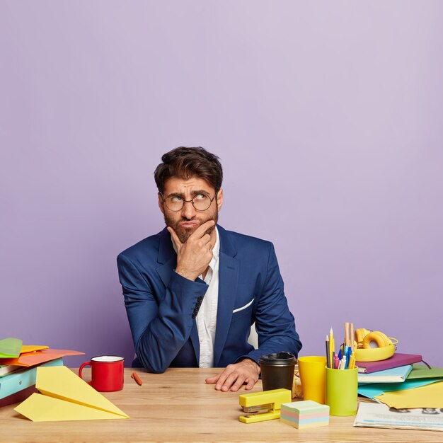 Zdjęcie Przemyślanego Biznesmena Siedzącego Przy Biurku Darmowe Zdjęcia