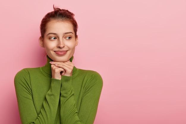 Zdjęcie Przemyślanej, Przyjemnie Wyglądającej Europejki Trzymającej Obie Ręce Pod Brodą, Odwracającej Wzrok, Ubrana W Zielony Swobodny Sweter, Odizolowana Na Różowej ścianie, Wolne Miejsce Na Bok Darmowe Zdjęcia