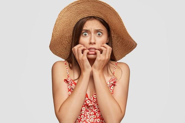 Zdjęcie Przestraszonej, Przestraszonej Kobiety Rasy Kaukaskiej Z Zielonymi Oczami, Zaciska Zęby Ze Strachu, Trzyma Ręce Przy Ustach Darmowe Zdjęcia