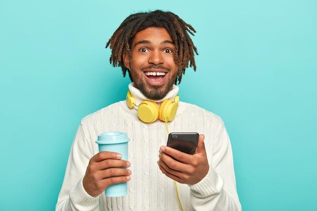 Zdjęcie Przystojnego Wesołego Mężczyzny Z Dredami, Trzymającego Nowoczesny Telefon Komórkowy I Kawę Na Wynos, Ze Słuchawkami Darmowe Zdjęcia