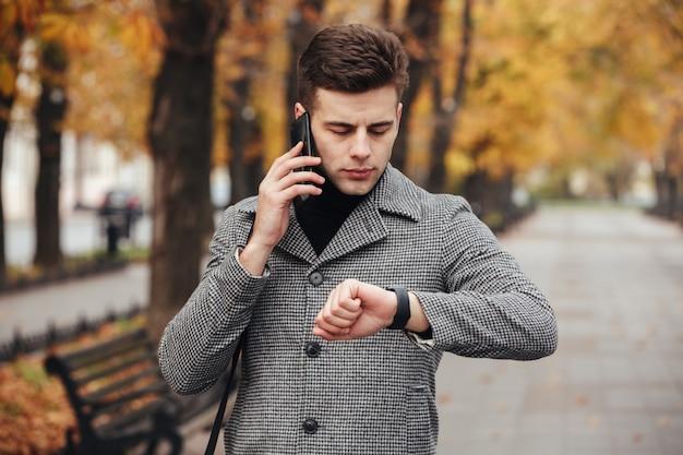 Zdjęcie Sprawnego Człowieka Mówiącego Na Telefon Komórkowy Podczas Spotkania, Sprawdzania Czasu Z Zegarkiem Na Rękę Darmowe Zdjęcia