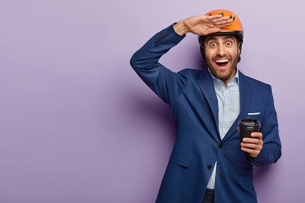 Zdjęcie Szczęśliwego Europejczyka Trzymającego Dłoń Przy Czole, Pije Kawę Na Wynos, Nosi Nakrycie Głowy I Formalny Garnitur, Próbuje Zobaczyć Coś W Oddali Darmowe Zdjęcia