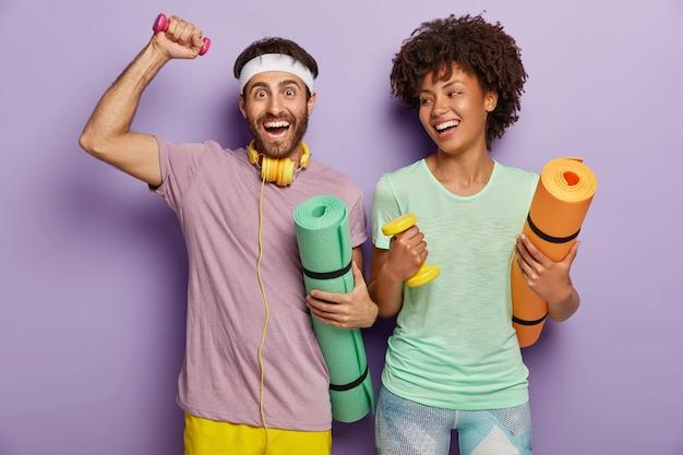 Zdjęcie Szczęśliwego Faceta I Kobiety Pracują Na Bicepsach Z Ciężarami, Noszą Karematy, Mają Radosne Miny, Cieszą Się Wspólnym Treningiem, Są Ubrani W Codzienne Stroje, Są Zmotywowani Do Zdrowego Stylu życia I Sportu Darmowe Zdjęcia