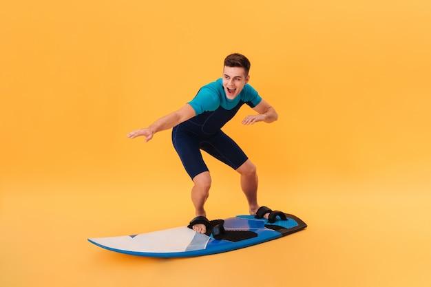 Zdjęcie Szczęśliwego Surfera W Kombinezonie Przy Użyciu Deski Surfingowej Jak Na Fali Darmowe Zdjęcia