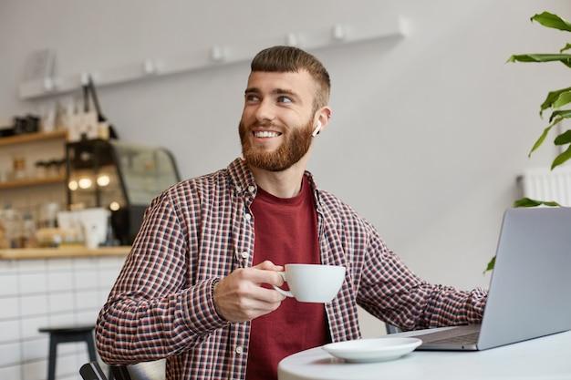 Zdjęcie Szczęśliwego Uśmiechniętego Atrakcyjnego Rudobrodego Mężczyzny Pracującego Przy Laptopie, Siedzącego W Kawiarni, Pijącego Kawę, Noszącego Podstawowe Ubrania, Patrzącego W Prawo, Dzięki Barista Za Wspaniałą Kawę. Darmowe Zdjęcia