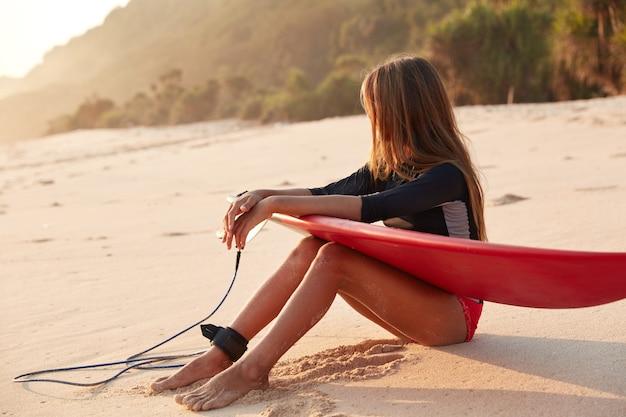 Zdjęcie Szczupłego Surferki W Stroju Kąpielowym, Robi Sobie Przerwę Po Surfowaniu Na Dużych Falach Oceanu Darmowe Zdjęcia