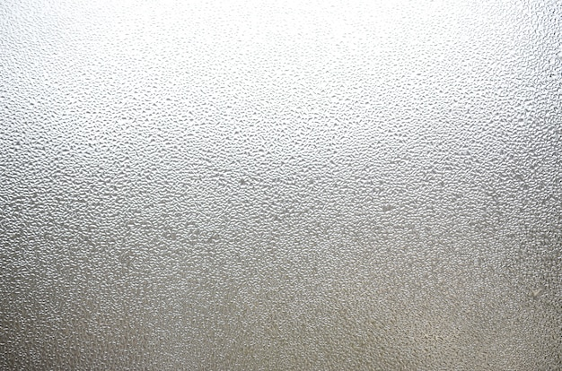 Zdjęcie szklanej powierzchni okna, pokryte wieloma kroplami o różnych rozmiarach. tekstura tło gęstej warstwy kondensatu na szkle Premium Zdjęcia