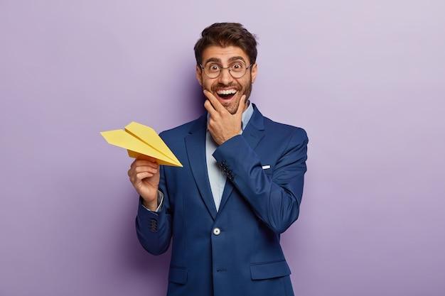 Zdjęcie Wesołego Zamożnego Biznesmena Jest Właścicielem Dużej Firmy, Pozytywnie Się Uśmiecha, Nosi Przezroczyste Okulary I Garnitur, Rzuca Papierowy Samolot Darmowe Zdjęcia
