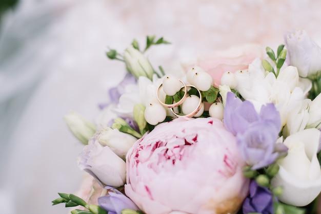 Zdjęcie z obrączkami leży na bukiecie kwiatów Premium Zdjęcia