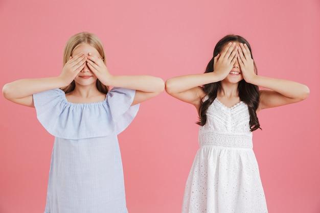 Zdjęcie Zabawnych Małych Dziewczynek W Wieku 8-10 Lat Ubranych W Sukienki I Zakrywające Oczy Rękami, Na Białym Tle Na Różowym Tle Premium Zdjęcia