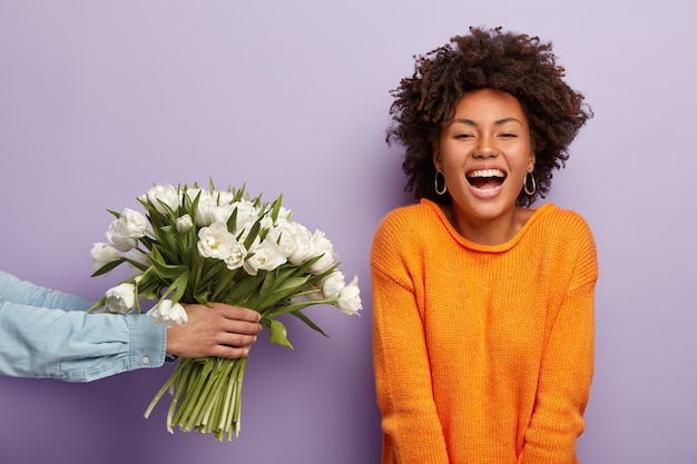 Zdjęcie Zachwyconej Afroamerykanki Szczerze Się śmieje, Dostaje Kwiaty Od Męża Lub Chłopaka Darmowe Zdjęcia