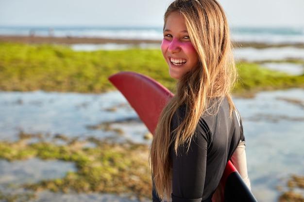 Zdjęcie Zadowolonej Długowłosej Kobiety Trzymającej Pod Ręką Deskę Surfingową, Wygląda Pozytywnie Darmowe Zdjęcia
