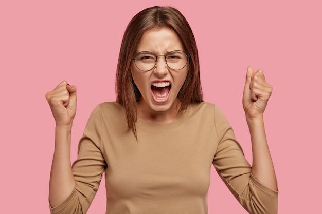 Zdjęcie Zdenerwowanej Gospodyni Domowej, Która Pokłóciła Się Z Sąsiadem, Podnosi Ręce Zaciśnięte W Pięści, Krzyczy Ze Złości Darmowe Zdjęcia