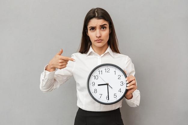 Zdjęcie Zdezorientowanej Lub Zdenerwowanej Młodej Kobiety W Białej Koszuli I Czarnej Spódnicy Wskazującej Palcem Na Dużym Okrągłym Zegarze Trzymającej W Ręku, Odizolowanej Na Szarej ścianie Premium Zdjęcia