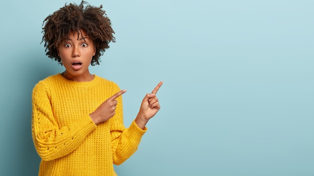 Zdjęcie Zdumiewająco Przystojnej Kobiety, Krzyczy Z Szokujących Wiadomości, Wskazuje Na Prawy Pusty Róg, Nosi żółty Sweter, Zaskoczona Niespodziewaną Ceną, Coś Pokazuje. Skopiuj Miejsce Na Ogłoszenie Darmowe Zdjęcia
