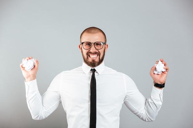 Zdjęcie Zirytowany Zły Biznesmen W Białej Koszuli I Okularach Gnije Dokumenty Papierowe W Obu Rękach, Odizolowane Na Szarej ścianie Premium Zdjęcia