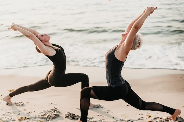 Zdrowa Dysponowana Kobieta ćwiczy Joga Z Opiekunem Fitness Na Plaży Blisko Oceanu Premium Zdjęcia