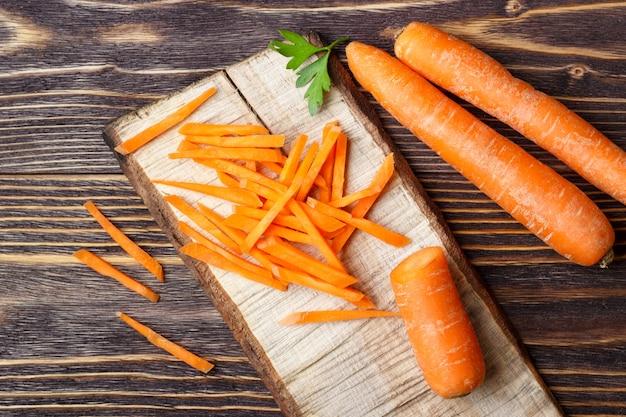 Zdrowe Jedzenie - Cała I Pokrojona Marchewka Na Drewnianym Tle. Premium Zdjęcia