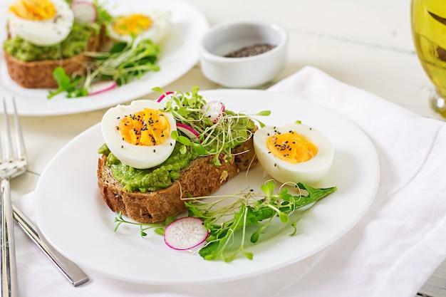Zdrowe Jedzenie. śniadanie. Jajeczna Kanapka Z Awokado Z Chlebem Pełnoziarnistym Na Białej Powierzchni Drewnianej. Premium Zdjęcia