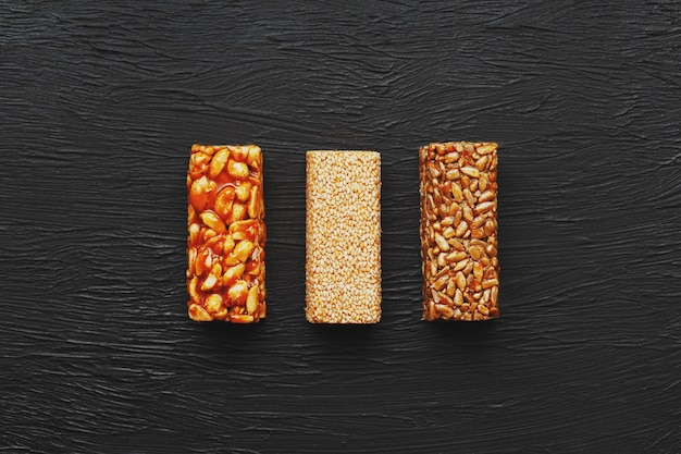 Zdrowe przekąski. jedzenie dietetyczne. ziarno z orzeszków ziemnych, sezamu i nasion na desce do krojenia na ciemnym stole, batony energetyczne Premium Zdjęcia