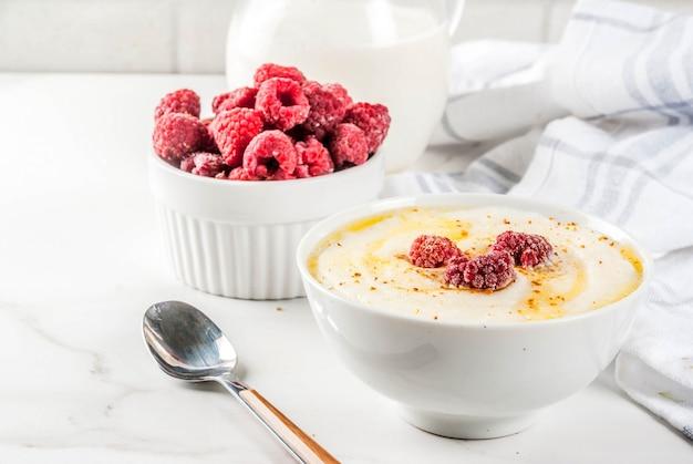 Zdrowe śniadanie, Kasza Manna Z Mlekiem I Malinami, Stół Z Białego Marmuru Premium Zdjęcia