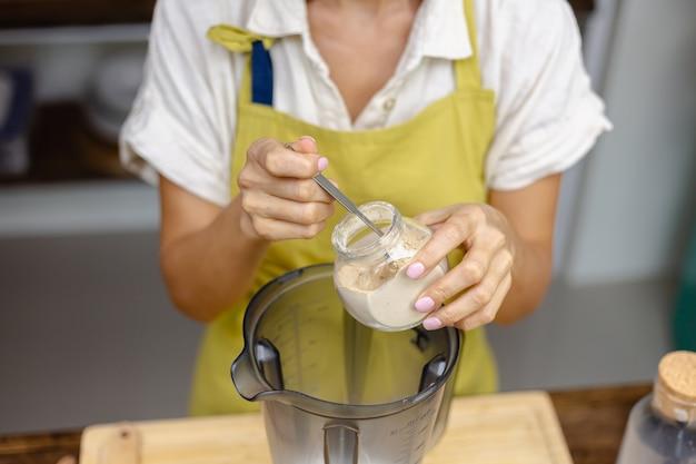 Zdrowe śniadanie Proces Produkcji Budyniu Chia. Kobieta łączy Nasiona Chia, Mleko Migdałowe I Naturalny Różowy Ekstrakt Ze Smoczego Owocu W Blenderze. Darmowe Zdjęcia