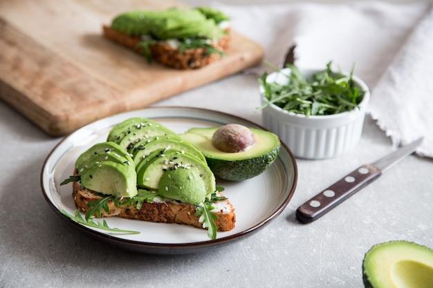 Zdrowe śniadanie z awokado i pyszne tosty całej pszenicy. Premium Zdjęcia