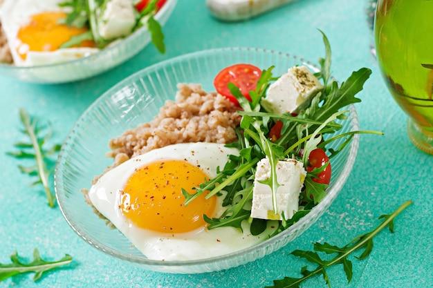 Zdrowe śniadanie Z Jajkiem, Serem Feta, Rukolą, Pomidorami I Kaszą Gryczaną Na Jasnym Tle. Odpowiednie Odżywianie. Menu Dietetyczne. Premium Zdjęcia