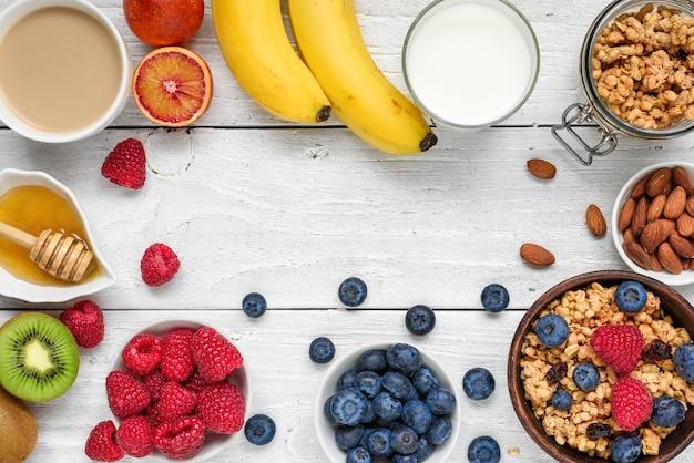 Zdrowe śniadanie Z Musli, Owocami, Jagodami, Cappuccino I Orzechami Na Białym Drewnianym Stole Premium Zdjęcia