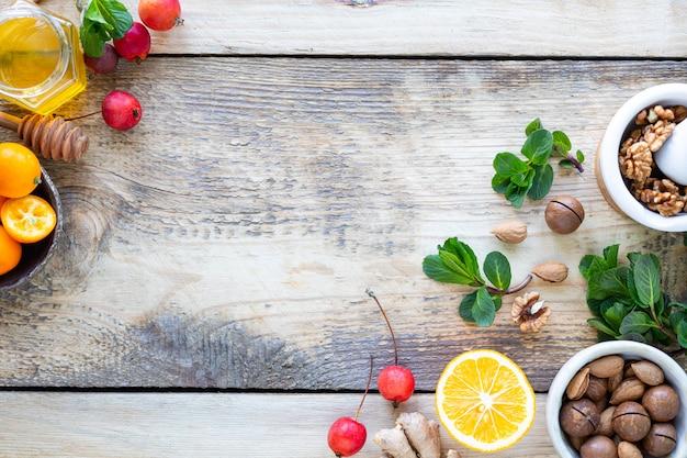 Zdrowi Produkty Dla Odporności Zwiększającej Na Drewnianym Tle Z Kopii Przestrzeni Odgórnym Widokiem. Cytryna, Orzechy, Imbir Na Układ Odpornościowy Premium Zdjęcia