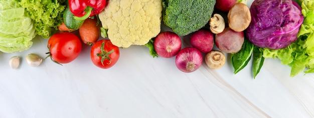 Zdrowi warzywa na marmurowym kuchennym kontuaru sztandaru tle Premium Zdjęcia