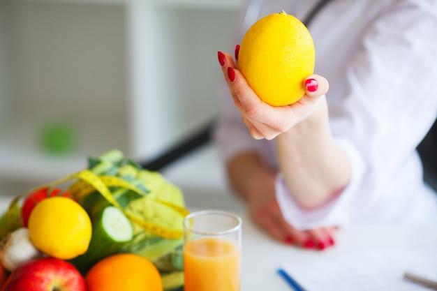 Zdrowie. Doktor Dietetyk Uśmiecha Się I Pokazuje Cytrynę. Premium Zdjęcia