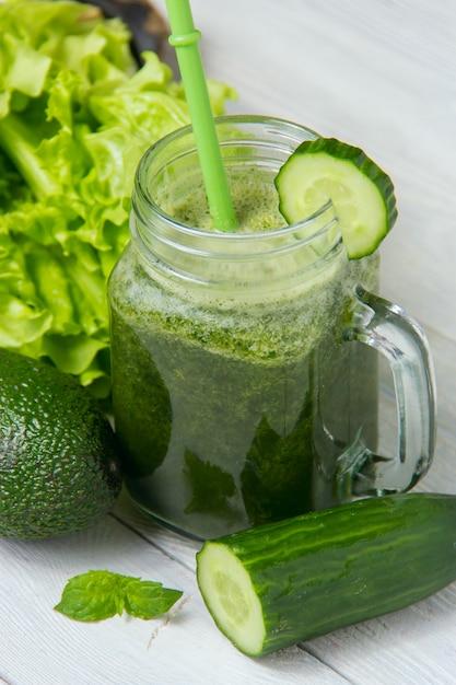 Zdrowy zielony smoothie z składnikami na białym drewnianym tle Premium Zdjęcia