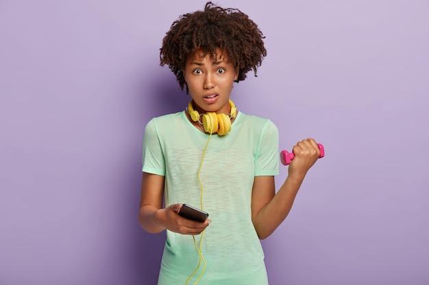 Zdziwiona Ciemnoskóra Kobieta Trzyma Smartfon I Wybiera Utwór Fitness Z Playlisty Na Telefonie Komórkowym Darmowe Zdjęcia