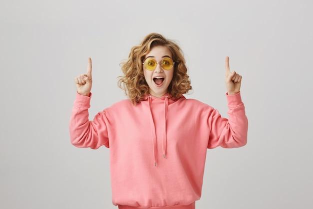 Zdziwiona I Zaskoczona Dziewczyna W Okularach Przeciwsłonecznych, Wskazując Palcami W Górę Darmowe Zdjęcia