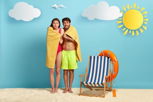 Zdziwiona Kobieta I Mężczyzna Drżą Pod Ręcznikiem, Marzną, Próbują Się Ogrzać Po Kąpieli Darmowe Zdjęcia