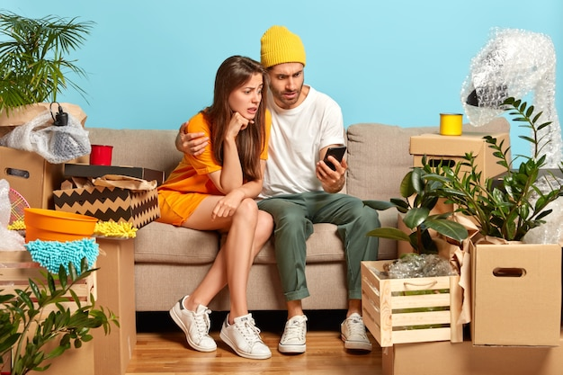 Zdziwiona Kobieta I Mężczyzna Patrzą Na Smartfony, Przeprowadzają Się Do Nowego Mieszkania, Szukają Mebli Do Swojego Mieszkania W Sklepie Internetowym Darmowe Zdjęcia