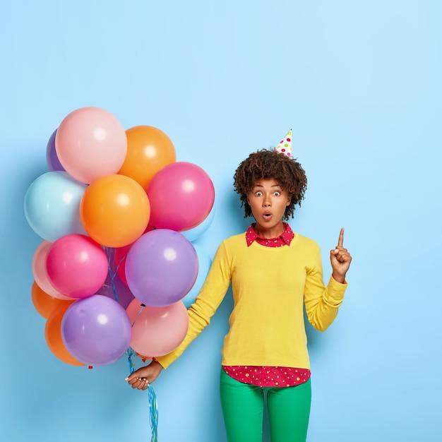 Zdziwiona Kobieta Pozuje W żółtym Swetrze, Trzymając Różnokolorowe Balony Darmowe Zdjęcia