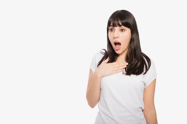 Zdziwiona kobieta utrzymuje rękę na klatce piersiowej Darmowe Zdjęcia