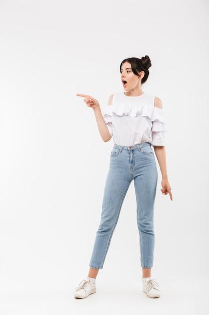 Zdziwiona Kobieta Z Fryzurą Double Buns Wskazując Palcem Na Bok Na Copyspace, Na Białym Tle Premium Zdjęcia