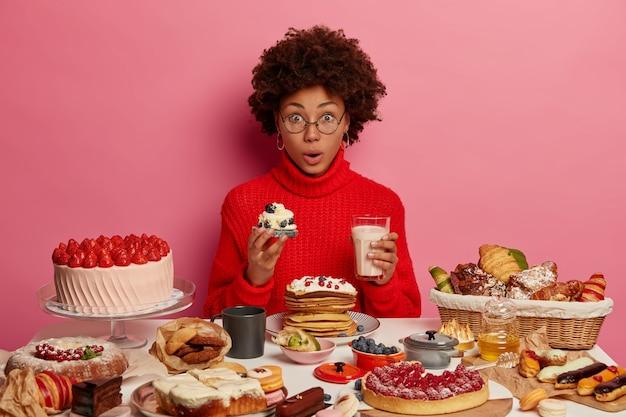Zdziwiona Młoda Afro Kobieta Lubi Jeść Pyszne, Pyszne Ciastko Z Jogurtem, Lubi Uroczysty Obiad, Zszokowana, Ile Zjadła Kalorii, Nosi Czerwony Sweter, Smakuje Kremowy Deser Darmowe Zdjęcia