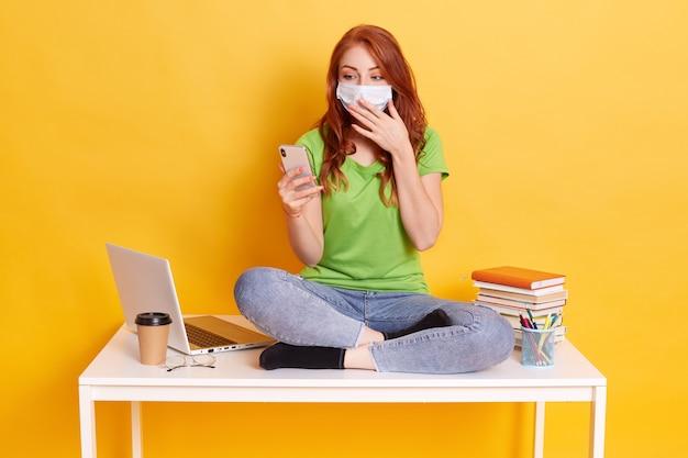 Zdziwiona Młoda Kobieta Otrzymała Wiadomość Sms-em Podczas Nauki, Trzymając Telefon Komórkowy I Zakrywając Usta Dłonią, Nosiła Maskę Medyczną I Zwykłe Ubranie, Siedząc Na Stole Ze Skrzyżowanymi Nogami. Darmowe Zdjęcia